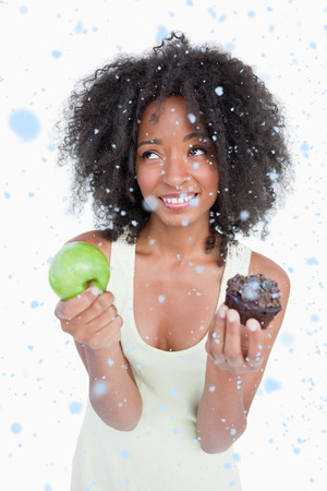 Young woman looking up to ask for help to choose between a fruit and chocolate against snow falling photo