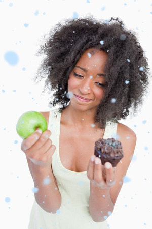 Young woman hardly hesitating between a muffin and an apple against snow falling photo