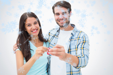 Happy young couple showing new house key against snow falling photo