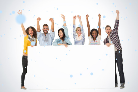 Smiling group of young friends showing large poster and cheering against snow falling Stock Photo