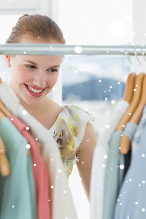 Beautiful female customer selecting clothes at store against snow falling photo