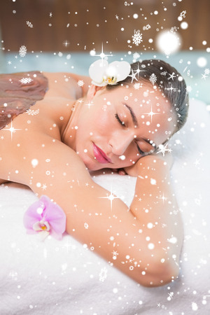 Attractive woman receiving chocolate back mask at spa center against snow falling photo