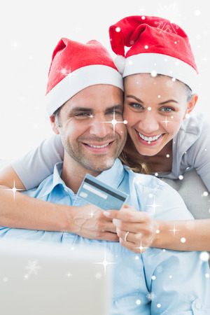 Happy couple in santa hats shopping online against snow falling photo