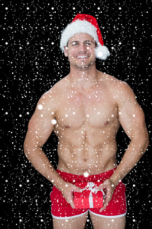 pere noel sexy: Sourire homme musclé posant en père noël sexy costume tenant cadeau contre des chutes de neige Banque d'images