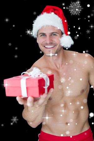 neige qui tombe: Sourire homme musclé posant en père noël sexy tenue offrant cadeau contre des chutes de neige