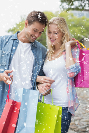 Hip young couple looking at their shopping bags against snow falling photo