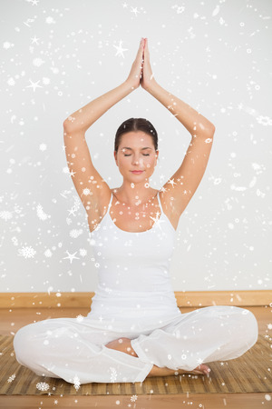 Peaceful brunette sitting and meditating in lotus pose against snow falling photo