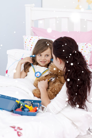 Composite image of Mother and sick daughter playing with a stethoscope with snow falling photo