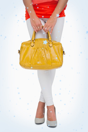 Composite image of Woman in high heels holding yellow bag with snow falling photo
