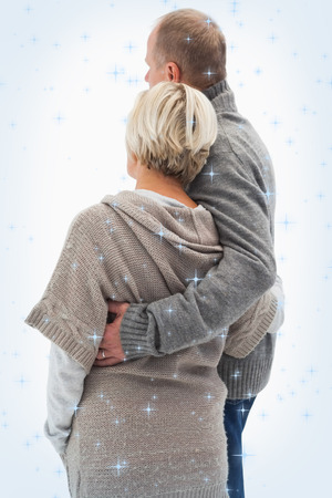 Composite image of Happy mature couple in winter clothes with night sky photo