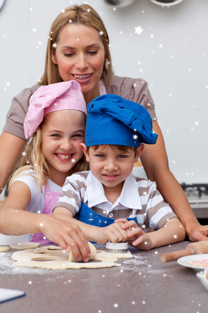 Mother helping her children baking with twinkling stars photo