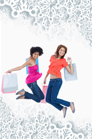 energetically: Young teenagers energetically jumping after going shopping against snowflakes on silver Stock Photo