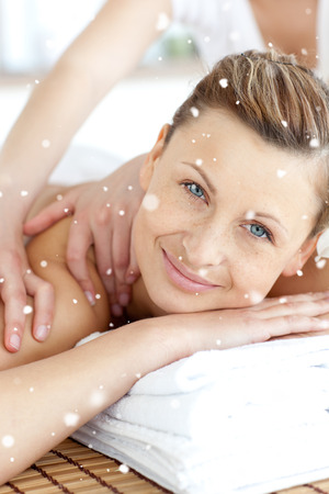 Cheerful woman enjoying a back massage with snow falling photo