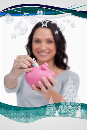 Money being put into piggy bank by woman against christmas frame photo