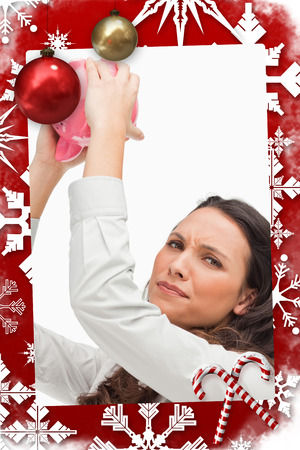 Portrait of a brunette woman holding an empty piggy bank against christmas themed page photo