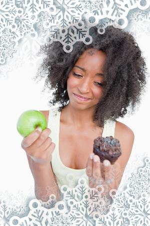 dudando: Mujer joven casi no dudando entre una magdalena y una manzana contra los copos de nieve en la plata Foto de archivo