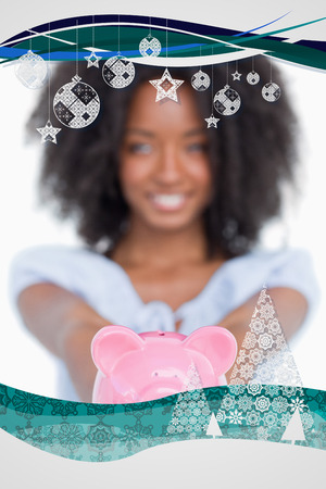 Pink piggy bank held by a young smiling woman with curly hair against christmas frame photo