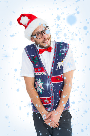 Geeky hipster in santa hat against snow falling photo