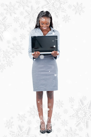 Composite image of Portrait of a businesswoman showing a laptop with snowflakes photo