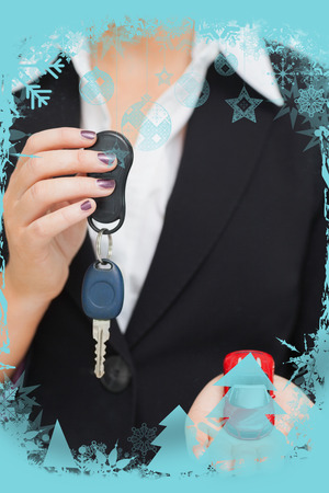 Composite image of Woman holding key and small car in her palm in a christmas frame photo