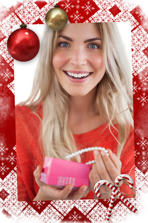 Composite image of Cheerful woman discovering necklace in a gift box in a christmas themed page photo
