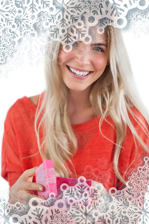 Composite image of Smiling woman with gift box with snowflakes on silver photo