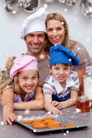 Happy children and parents eating biscuits with snow falling photo