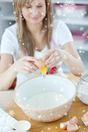 gratified: Attractive woman preparing a cake in the kitchen with snow falling