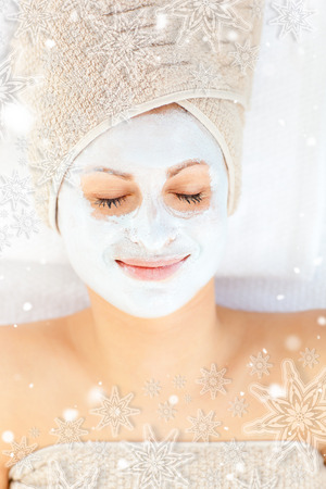 Cute young woman with closed eyes having white cream on her face with snowflakes photo