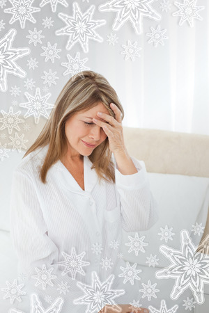 vexation: Woman having a headache on her bed with snowflakes on silver