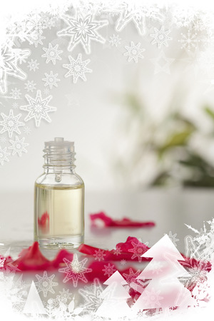 Composite image of glass phial and pink petals in a christmas frame photo