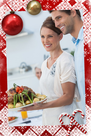 Cheerful couple showing roast chicken in the kitchen against christmas themed page photo