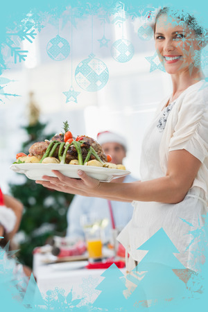 Attractive woman bringing roast chicken at a christmas dinner against christmas frame photo