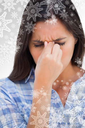 wincing: Brunette wincing with headache pain against snowflakes on silver