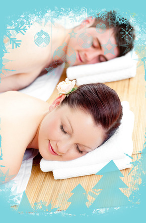 Resting couple lying on a massage table against christmas frame photo