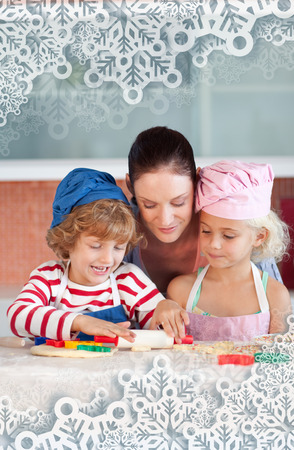 Joyful mother baking with her children against snowflakes on silver photo