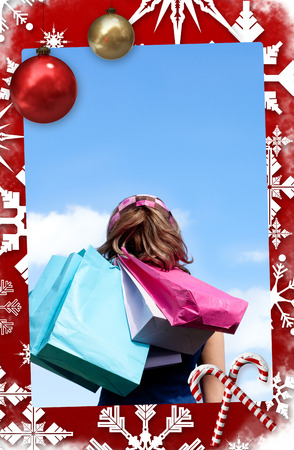 gratified: Smiling woman holding shopping bags outdoor  against christmas themed page