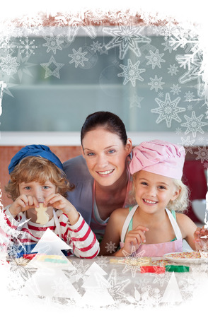 Cheerful mother baking with her children against christmas frame photo