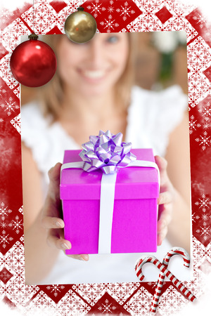 Young woman holding a present sitting on the floor against christmas themed page Stock Photo