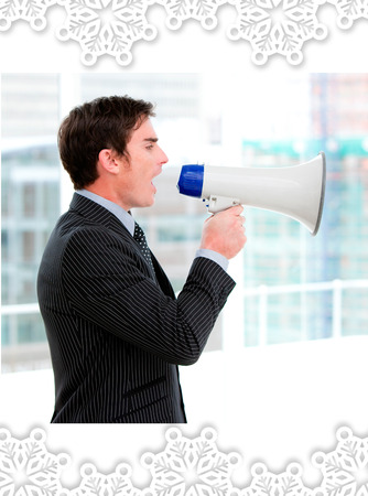 Frustrated businessman yelling through a megaphone  against snowflake frame photo