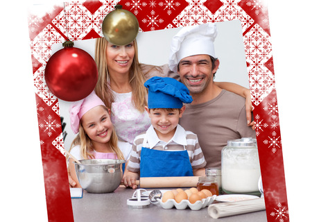 Smiling parents helping children baking in the kitchen against christmas themed page photo