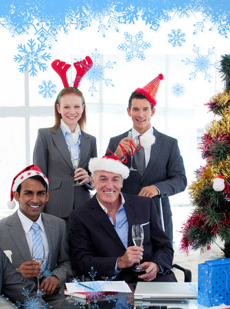 Smiling business people wearing novelty Christmas hat against snow flake frame in blue photo