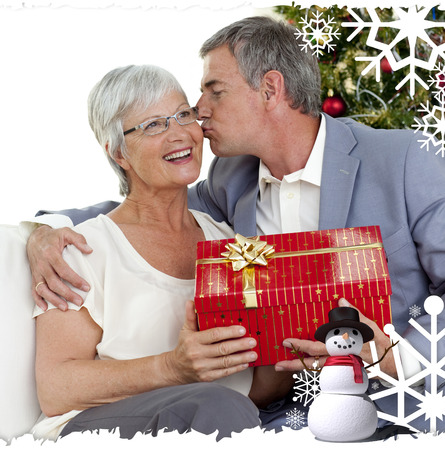 Senior man giving a kiss and a Christmas present to his wife against christmas themed frame photo