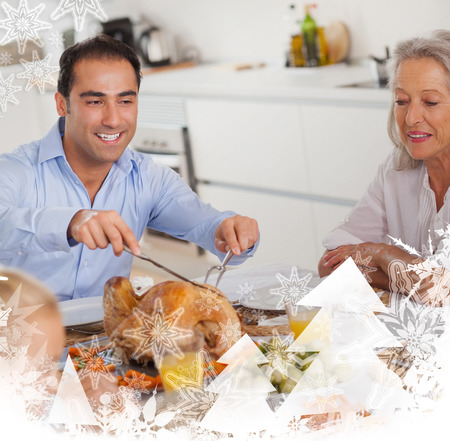 Man carving the thanksgiving turkey against christmas frame photo
