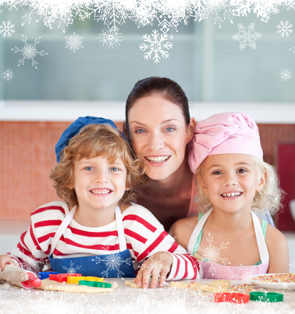 Radiant mother baking with her children against fir tree forest and snowflakes photo