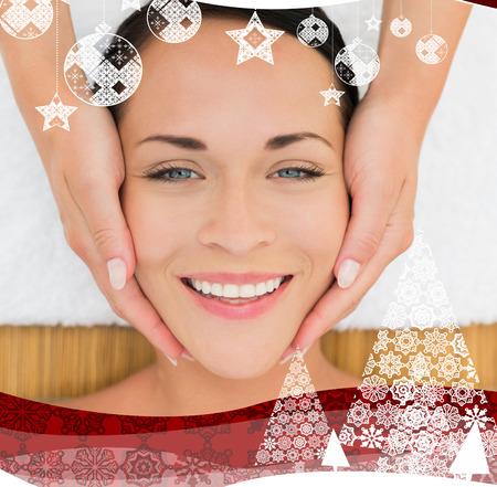 Peaceful brunette enjoying a facial massage against christmas themed frame photo