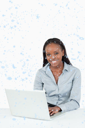Composite image of Portrait of a smiling businesswoman using a laptop with snow falling photo