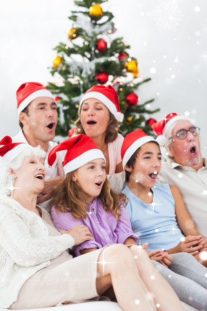 Extended family singing christmas carols against snow falling photo
