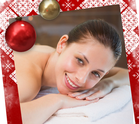 Beautiful woman lying on massage table at spa center against christmas themed page photo