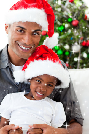 Composite image of Father and daughter wearing a Christmas hat with snow falling photo